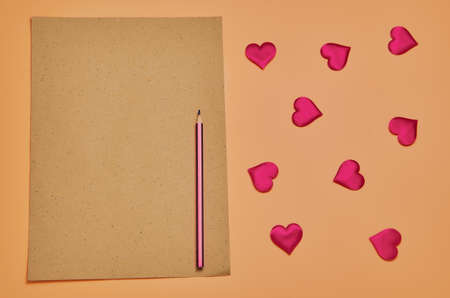 A clean sheet of crafted brown paper with a pencil rests on a beige background. Frame of red Decorative little hearts. Flat lay. A place to copy.