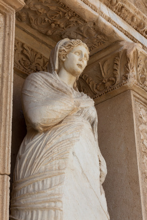 by virtue: The library of Celsus is an ancient Roman building in Ephesus,  with Arete statue personification of virtue. Stock Photo