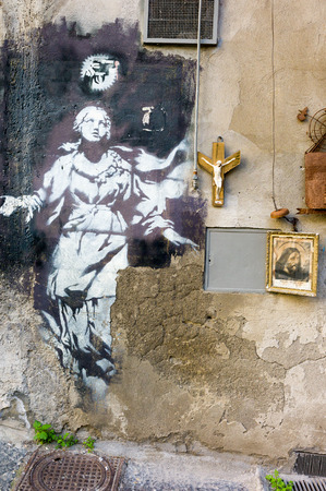 Naples, Italy,  - January 17, 2016: Full view of the placed artwork by artist Bansky in  gerolomini square, painted in 2013 Editöryel