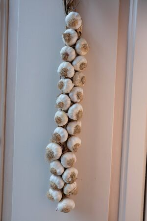 leaning against: Neapolitan garlic braid leaning against the wall Stock Photo