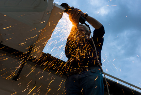 worker cutting metal with circular saw producing sparks
