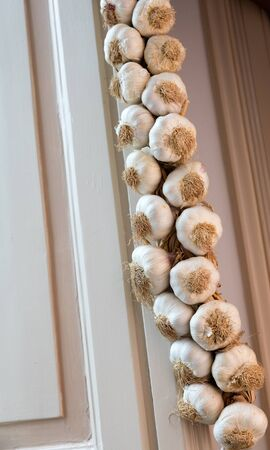 Neapolitan garlic braid leaning against the wall Stock Photo