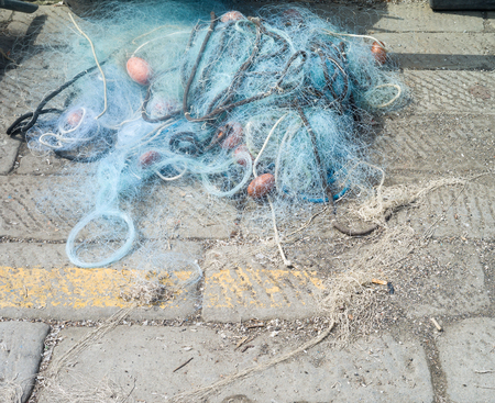 fishing net laid out on a pier Stock Photo