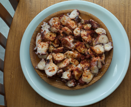 Wooden plate of galician style cooked octopus with paprika and olive oil.