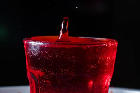 drops of red liquid in glass beaker