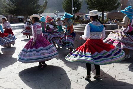 Peruvian girls with typical Andean costumes dancing in the main square of a village