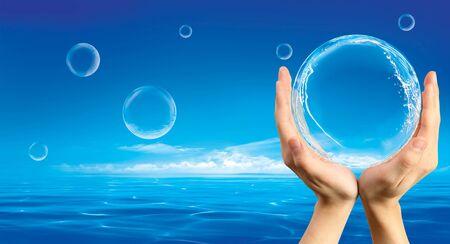 Handen een zeep bel met spashes binnen te houden tegen de achtergrond van een oceaan