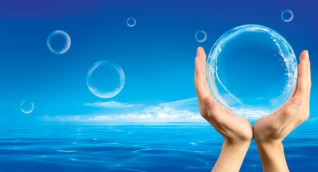 Hands holding a bubble with spashes inside against an ocean background photo
