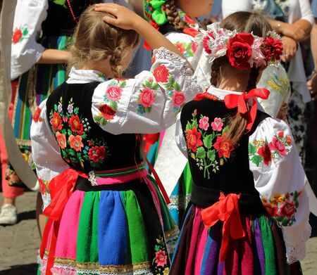 real people dressed in regional folk costumes from Lowicz region, Poland, during annual Corpus Christi procession, in front of two girls, one touches her head, stand on their back