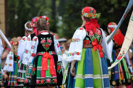 Women and girls in traditional folk costume from Lowicz region, Poland, march in Corpus Christi procession