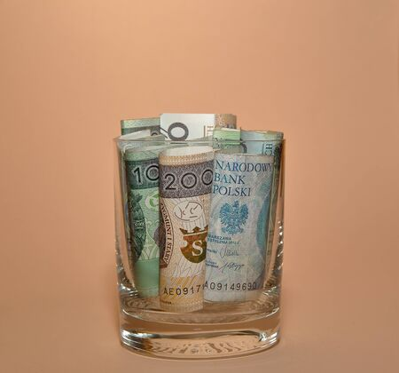 Lots of Polish 200 and 100 Polish zloty rolls into glass isolated on pastel peach background, close up