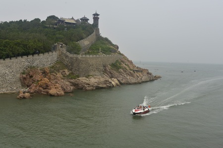 View of Penglai Pavilion and speedboat in the water Фото со стока