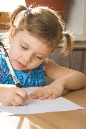 small girl learns to write, sits at a table