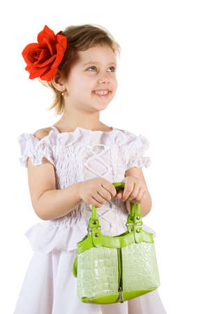 Little smiling girl with green bag and red rouses in the hair photo