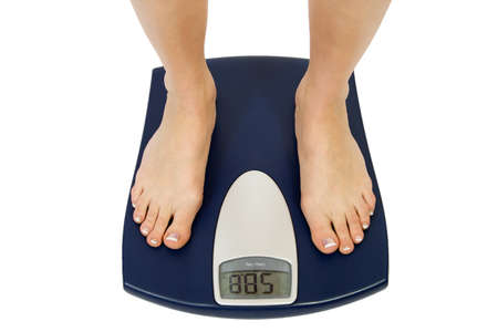kilograms: Female feet standing on a bathroom scale Stock Photo