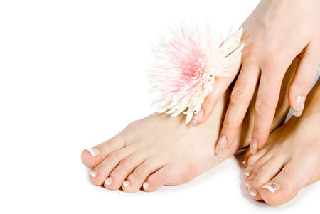 Womans foot and hand with flowers isolate on white