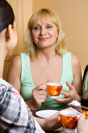 Mother and daughter drinking tea. Focus point on a mother. photo