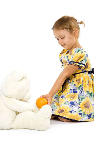 Little girl with orange and bear toy. Isolate on white background. Stock Photo - 1585132