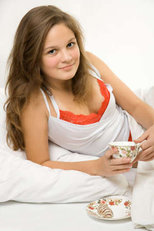 Young girl drinking tea in the bed photo