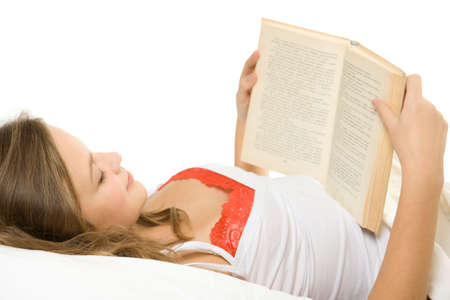 Young girl reading book in bed.