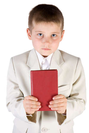 educating: Well-dressed boy hold in hands red book. Isolated on white