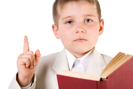 learned: Well-dressed boy read book and lift finger up. Isolated on white Stock Photo
