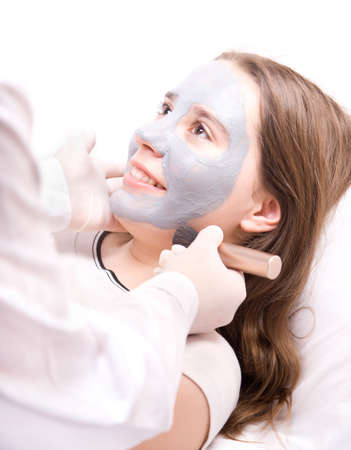 Beautician applying a clay mask on face young woman photo