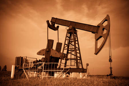 nonrenewable: Oil pump jack. Red filtered image. Stock Photo