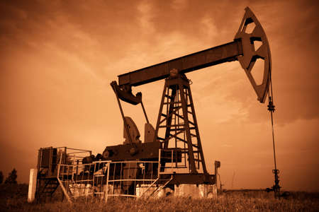 Oil pump jack. Red filtered image. Stock Photo