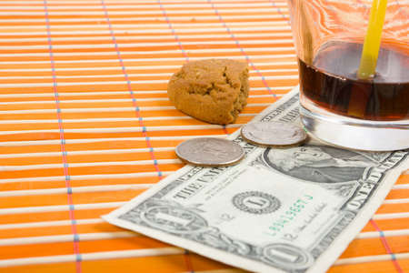 pay for: One dollar and 50 cent pay for drink and cookies on bamboo table-cloth Stock Photo