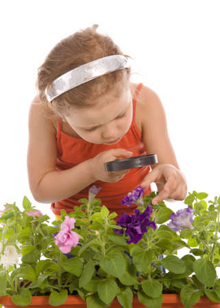 Young girl is looking through a magnifying glass and researching a flower