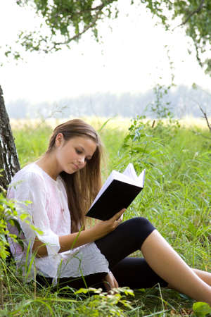 Young girl reading book in park in summer day photo
