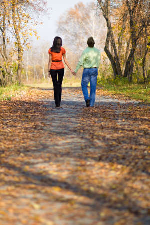 Young happy couple walking in the autumn park photo