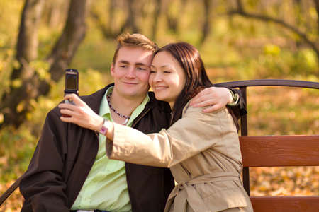 Young couple in park girl taking photo with mobile phone photo