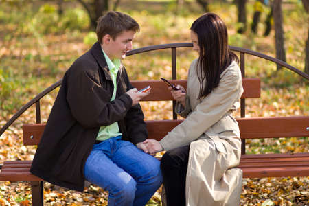 Young couple dial phone numbers a mobile phones photo