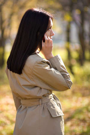 Pretty brunette caucasian girl calling by mobile phone photo