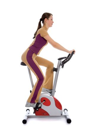Attractive woman doing fitness on a stationary bike isolated on white Stok Fotoğraf
