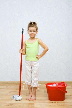 Little girl cleaning the floor in the room