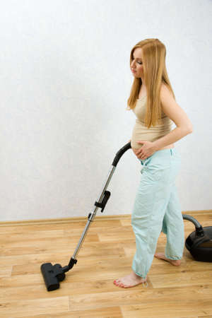 Pregnant caucasian woman cleaning floor with vacuum cleaner Stock Photo