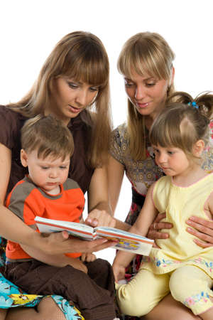 Two young mothers read books to their children photo