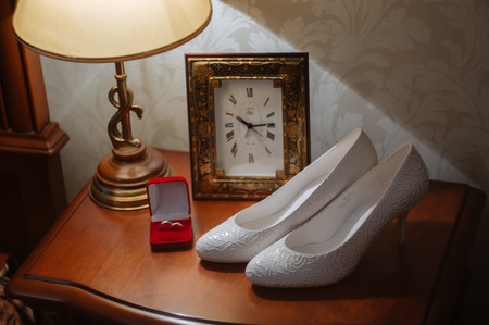 wedding rings in box on a nightstand with lamp and shoes Stok Fotoğraf
