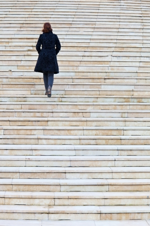 to climb: solitary woman walking up stairs