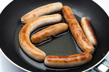 chorizos: sausages frying in a pan