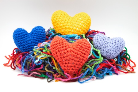 untidily: colors woolen hearts on white fund