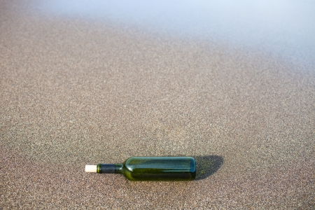 glass bottle on the sand photo