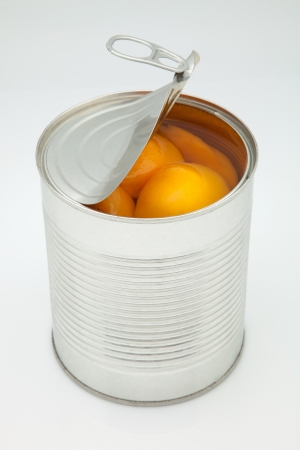 canned food: canister of peaches opened on white fund