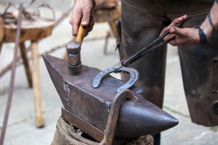 Farrier hits  horse shoe to change the shape photo