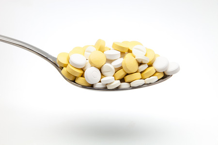 cold remedy: Spoon full of pills and capsules Stock Photo