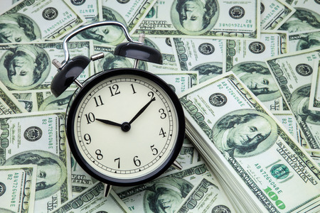 money sphere: alarm clock and banknotes of one hundred dollars Stock Photo