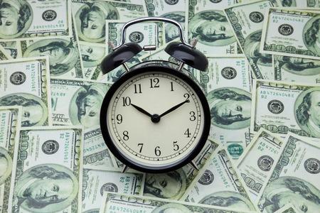 money savings: alarm clock on banknotes of one hundred dollars